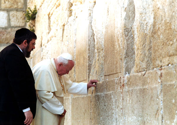 Rabbi Michael Melchior looks on as Pope John Paul II prays at the Western Wall, the holy site of Judaism, in Jerusalem March 26, 2000. (Photo: CNS)