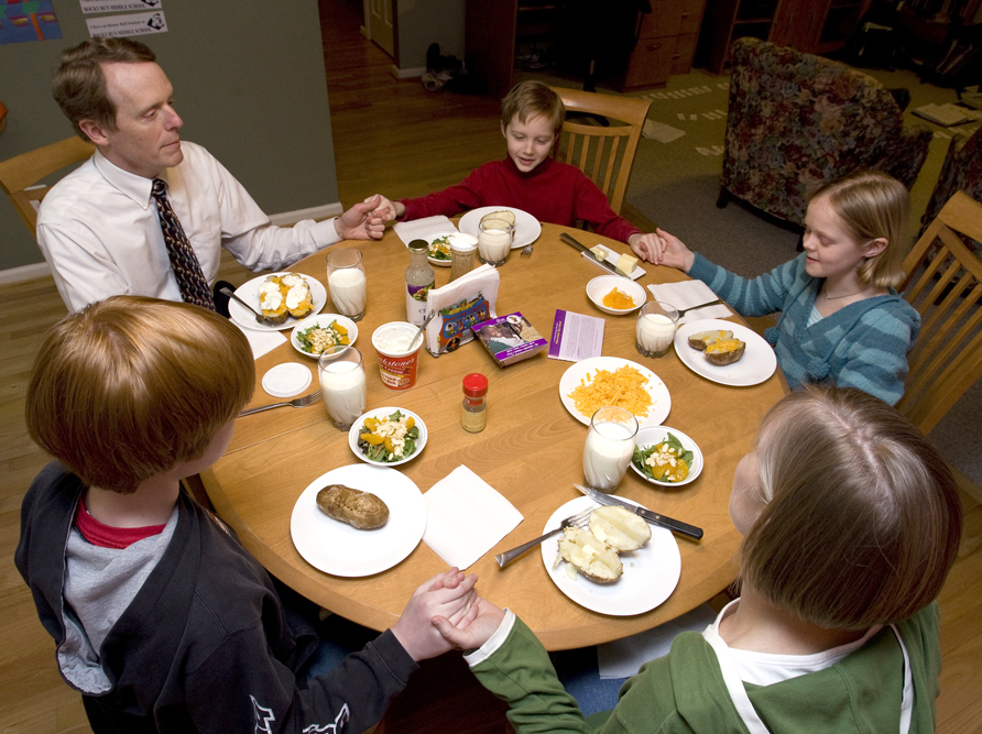 A family eats around the table, a place where we experience the true nature of community.