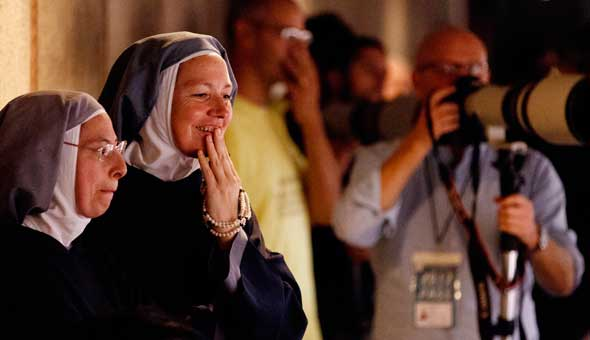 Nuns watch from a position used by news photographers during Pope Benedict XVI's general audience in Paul VI hall at the Vatican. (CNS photo/Paul Haring)