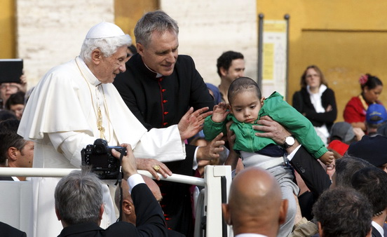 Pope Benedict XVI prepares to kiss a child as he leaves his general audience in St. Peter's Square at the Vatican on October 17. (CNS photo/Paul Haring)