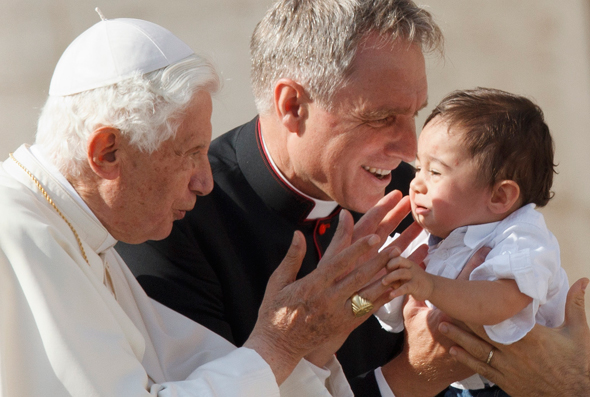 Pope Benedict greets a child as he leaves his general audience in St Peter's Square at the Vatican. Also pictured is Mgr Georg Ganswein, the pope's personal secretary. (CNS photo/Paul Haring)