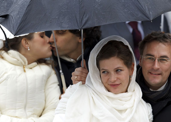 Newly married couples wait under umbrellas before Pope Benedict's general audience in St. Peter's Square at the Vatican (CNS photo/Paul Haring)