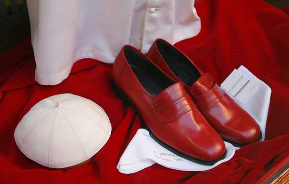 A papal zucchetto and red shoes are seen in the window of the Gammarelli clerical tailor shop in Rome. At the request of the Vatican the famous shop has prepared three sizes of clerical wear to be used by the new pope immediately after his election. (CNS photo/Paul Haring)