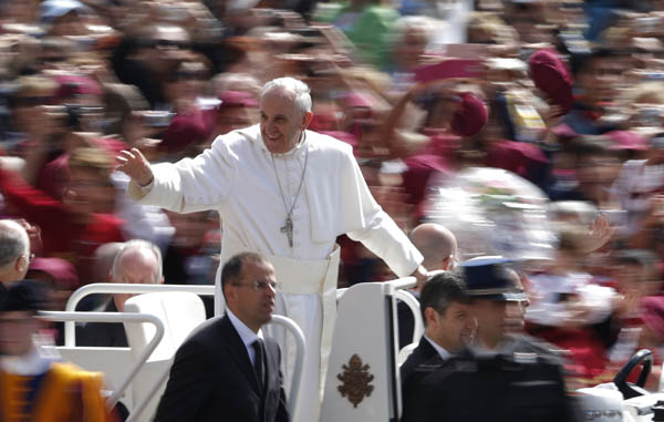 Pope Francis greets the crowd as he arrives to lead his general audience in St. Peter's Square at the Vatican on May 22. (CNS photo/Paul Haring)
