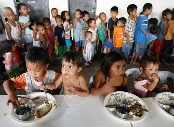 Children eat free meals  at a feeding centre of the World Mission Church, a nongovernmental agency, in a slum area in Manila, Philippines. (CNS photo/Romeo Ranoco, Reuters)