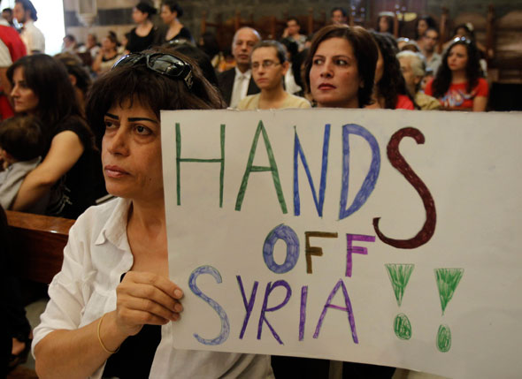 A woman holds up a sign during a prayer service for peace at the Melkite Catholic patriarchate in Damascus, Syria, Sept. 7. 2013. The service was held as people worldwide heeded Pope Francis' call for a day prayer and fasting for peace in Syria. (CNS photo/Khaled al Hariri, Reuters)