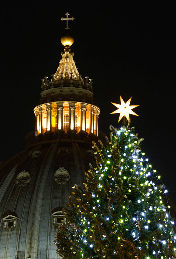 The cupola of St Peter's Basilica and the top of the Vatican Christmas tree are seen from St Peter's Square following a lighting ceremony Dec. 13. (CNS photo/Paul Haring)