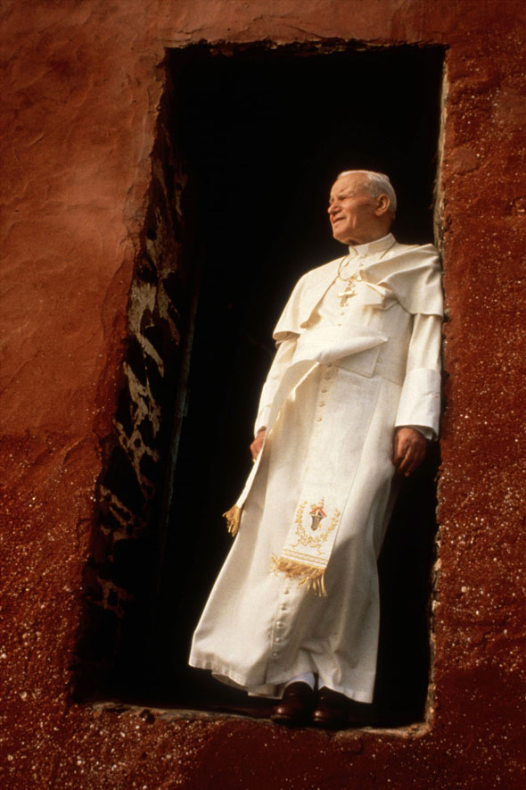 Pope John Paul II stands on the threshold of a former slave-trade depot on Goree Island during his 1992 trip to Senegal. The Polish pontiff and Blessed John XXIII will become saints in a ceremony presided over by Pope Francis April 27 at the Vatican. (CNS photo/Giancarlo Giuliani, Catholic Press Photo)
