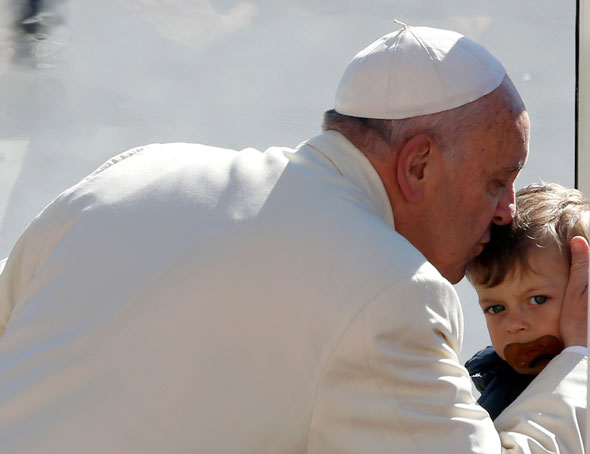 Pope Francis kisses a child as he arrives to lead his Wednesday general audience in St. Peter's Square at the Vatican April 16. (CNS photo/Stefano Rellandini, Reuters)