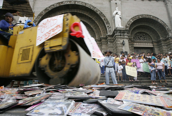 Pirated pornographic CDs and DVDs are crushed by a bulldozer outside the cathedral in Manila, Philippines. In August, the high court in Cape Town will hear arguments why pornographic content should not be broadcast in South Africa. (CNS photo/Romeo Ranoco, Reuters)