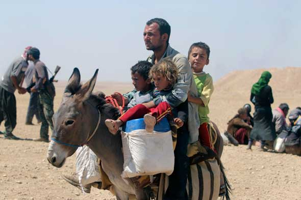A man and three children flee violence from forces loyal to the Islamic State in Sinjar, Iraq, Aug. 10. Islamic State militants have killed at least 500 Yezidi ethnic minorities, an Iraqi human rights minister said. (CNS photo/Rodi Said, Reuters)
