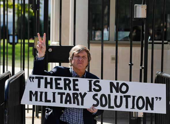 Father John Dear, a nationally known peace activist, gestures during a protest at the entrance to the White House in Washington Sept. 23. Father Dear and others blocked the gate to protest war, poverty and environmental destruction before being arrested by the police. (CNS photo/Larry Downing, Reuters)