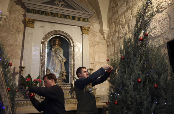 Priests decorate Christmas trees in St. Catherine's Church  (CNS photo/Nayef Hashlamoun, Reuters)