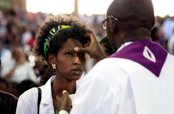 A priest marks a cross on the forehead of a woman during Ash Wednesday Mass at Holy Family Minor Basilica in Nairobi, Kenya. Catholics around the world began the penitential season of Lent with prayer, fasting and the mark of ashes. (CNS photo/Thomas Mukoya, Reuters)
