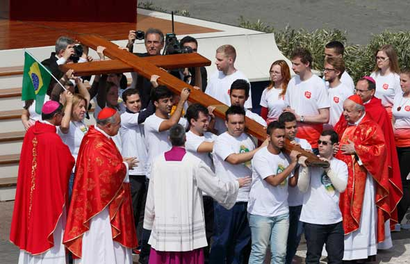 Young people from Brazil, left, pass on the World Youth Day cross to youths from Poland, right, at the conclusion of Pope Francis' celebration of Palm Sunday Mass in St. Peter's Square at the Vatican April 13. The next international Catholic youth gathe ring will be July 25-Aug. 1, 2016, in Krakow, Poland. (Photo: Paul Haring/CNS)