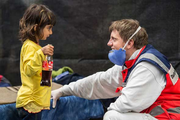 """A volunteer from the German Red Cross plays with a migrant girl from Syria in an emergency shelter in Rottenburg Sept. 16. """"Do not abandon victims"""" of conflicts in Syria and Iraq, Pope Francis pleads. (CNS photo/Wolfram Kastli, EPA)"""