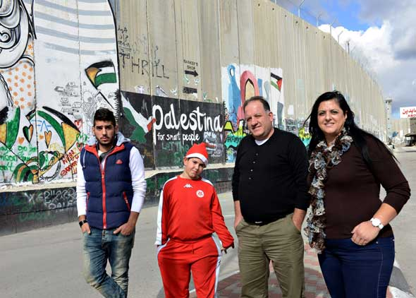 Afif and Nardin Hazboun of Nazareth with their sons, Fadi, 20 and Jowan, 8, in front of the Israeli separation wall in Bethlehem, West Bank. Afif Hazboun is following the tradition of yearly Christmas visits, which his father began when Afif was a child. (Photos: Debbie Hill/CNS)