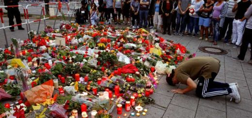 A man prays outside the Olympia shopping mall in Munich, Germany, July 23, where nine people were killed by an 18-year-old gunman. (CNS photo/Arnd Wiegmann, Reuters)
