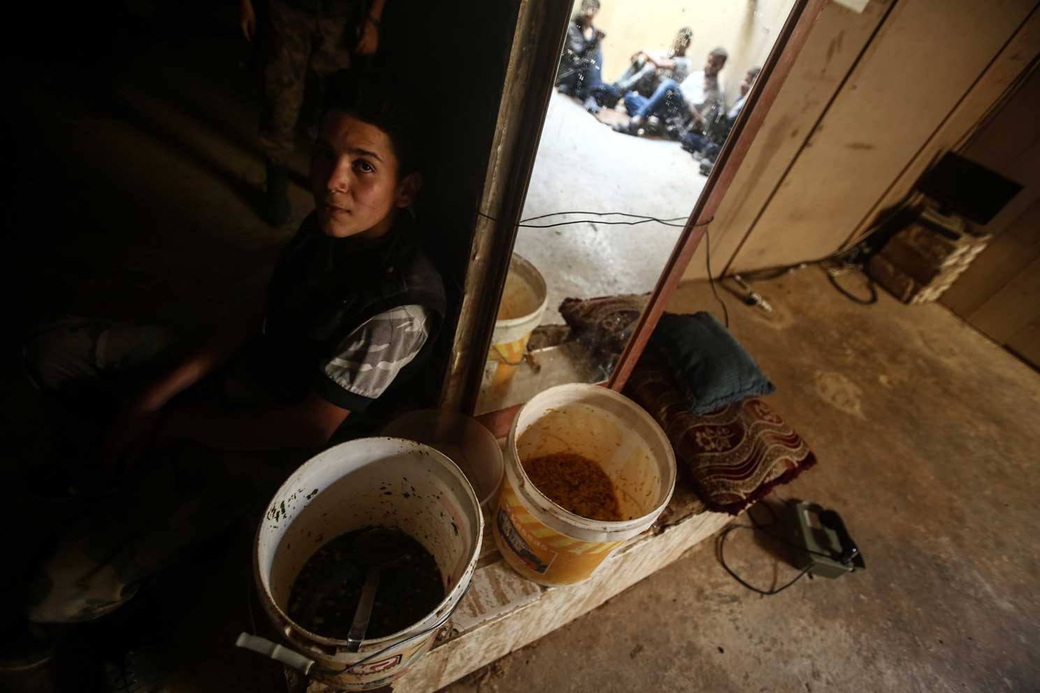 A Syrian fighter sits next to two food containers and a mirror in Douma, Syria July 28. Pope Francis said Aug. 7 that innocent men, women and children are paying the ultimate price in the continuing conflict raging in Syria. (CNS photo/Mohammed Badra, EPA)